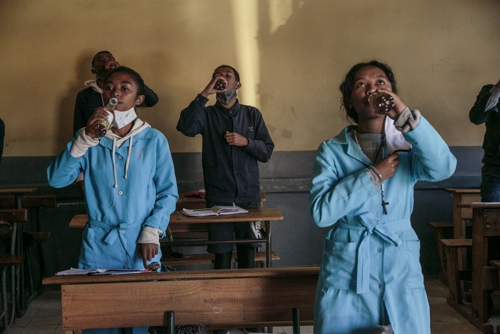 Students drink from bottles of Covid Organics, a herbal tea, touted by Madagascar President Andry Rajoelina as a powerful remedy against the Covid-19 coronavirus. (AFP)