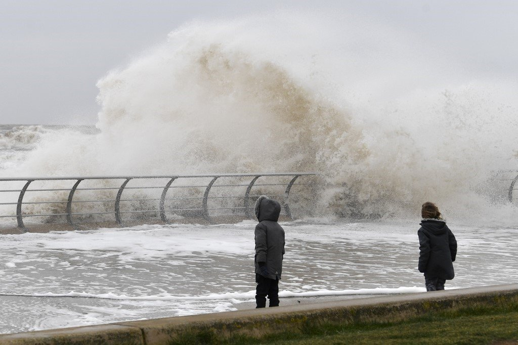 Children stand near the sea wall with over-topping waves
