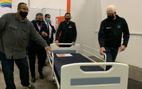 Western Cape Premier Alan Winde (right) and provincial head of Health Dr Keith Cloete (centre) help officials wheel out a hospital bed as the CTICC's Hospital of Hope is officially decommissioned on 21 August 2020. Picture: Kaylynn Palm/EWN